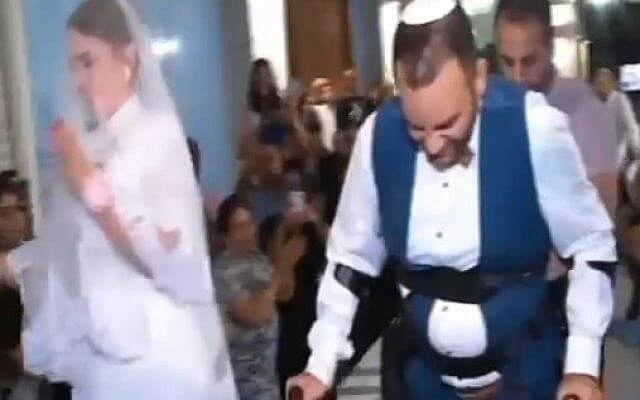 With the help of ReWalk Robotics, Dudu Shevy is able to walk down the aisle (screen capture: Channel 2)