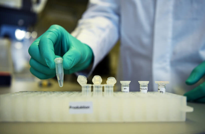An employee of German biopharmaceutical company CureVac, demonstrates research workflow on a vaccine for the coronavirus (COVID-19) disease at a laboratory in Tuebingen, Germany (photo credit: REUTERS/ANDREAS GEBERT)
